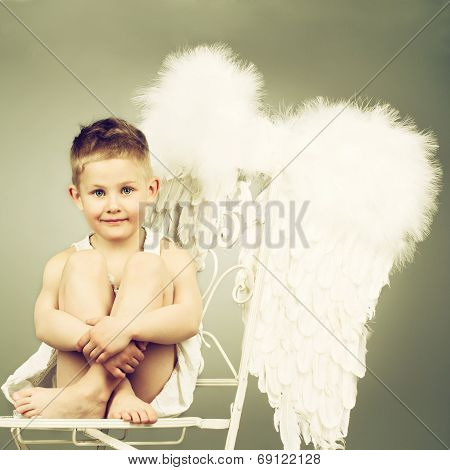 Smiling angel kid with white wings. Toned image