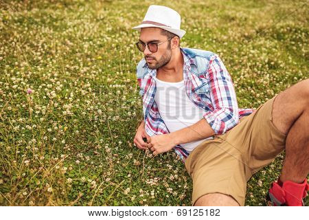 side view of a man lying down on a field and thinks