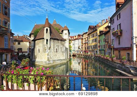 ANNECY, FRANCE - SEPTEMBER 17, 2012: Charming old town of Annecy in Provence. Clear early morning. Bastion- prison turned into  museum, is reflected in the water channel