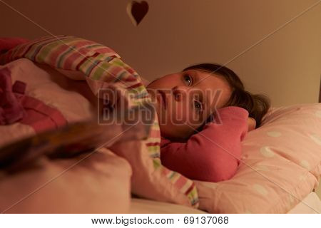 Worried Girl Lying In Bed Awake At Night