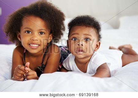 Sister With Baby Brother Lying On Parent's Bed