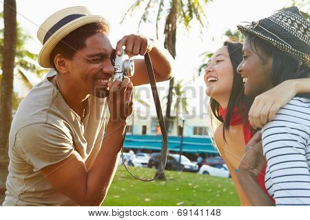 Man Taking Photograph Of Women In Park