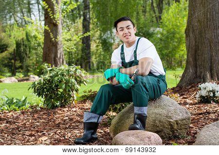 Gardener Sitting On A Rock