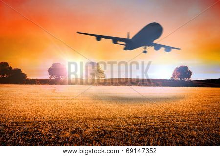 Composite image of airplane taking off against countryside scene