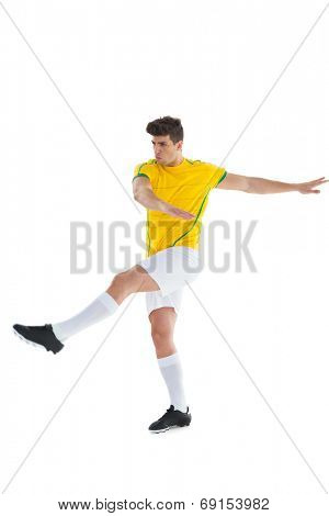 Football player in yellow jersey kicking on white background