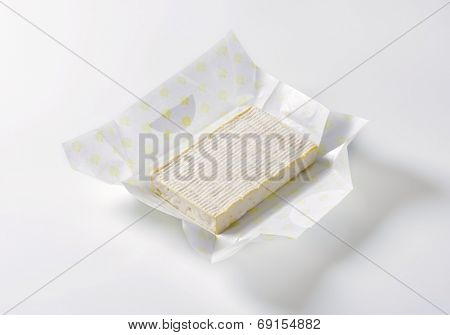 goat's milk cheese with white mold, in a paper wrapper