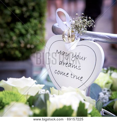 Floral wedding decorations with heart and rings,  and the message 'May your dreams come true'