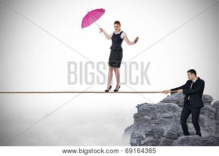Young businessman pulling a tightrope for businesswoman against rocky landscape