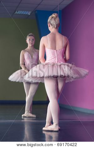 Graceful ballerina standing in first position in front of mirror in the ballet studio