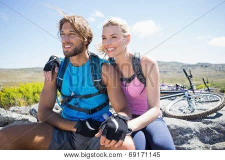 Fit cyclist couple taking a break on rocky peak on a sunny day