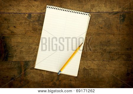 Note pad or memo pad on an old grungy wooden board or surface. For inserting your custom message or text.