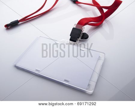 Blank ID card holder isolated with red neck strap, on glossy white desk.