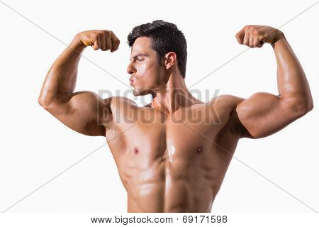 Portrait of a muscular young man flexing muscles over white background