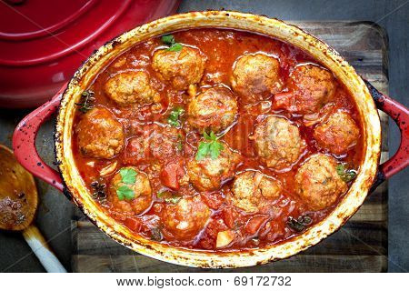Meatballs casserole in red iron crock pot.