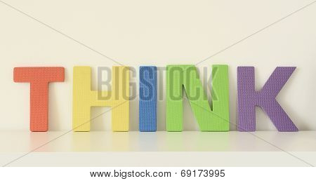 Word THINK, in colorful upper case letters of foam toys
