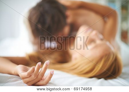 Hand of female lying on bed with a man caressing her
