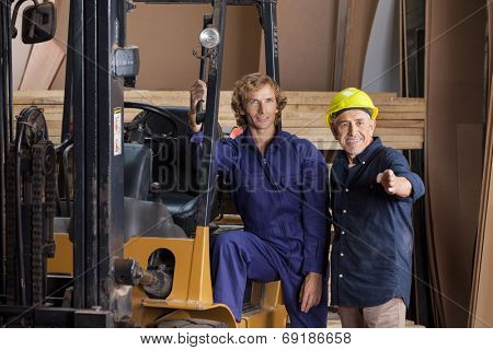 Male carpenters looking away while standing by forktruck in workshop