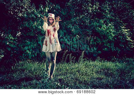 Woman zombie walking dead outdoors. Dark lighting. Color was changed to emphasize the atmosphere of horror.