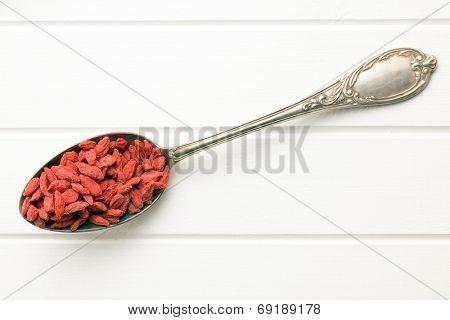 dried goji berries in silver spoon