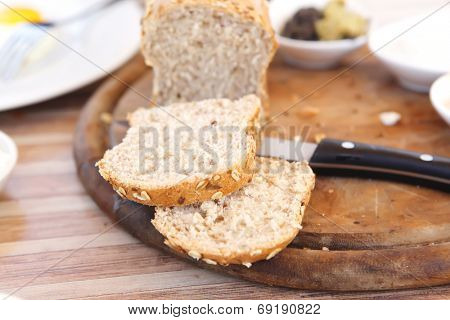 cut the home made bread on wooden board near tapas outside cafe