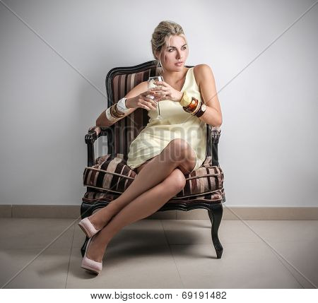 rich and attractive woman who is sitting on an armchair
