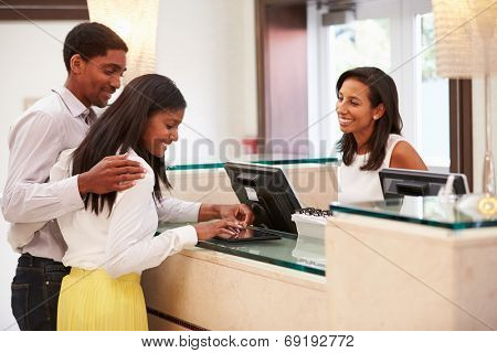 Couple Checking In At Hotel Reception Using Digital Tablet
