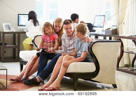 Family In Hotel Lobby Looking At Digital Tablet