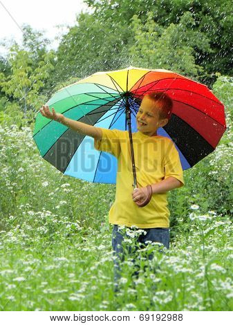 Playful boy hiding behind colorful umbrella outdoors