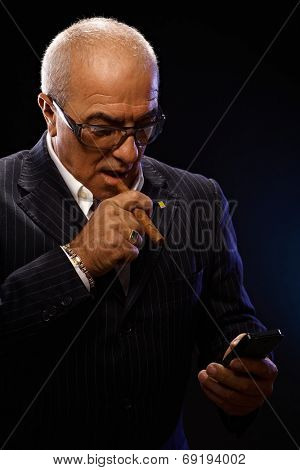 Portrait of maffia boss smoking cigar, using mobilephone.