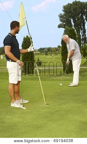 Young and old golfer playing together.