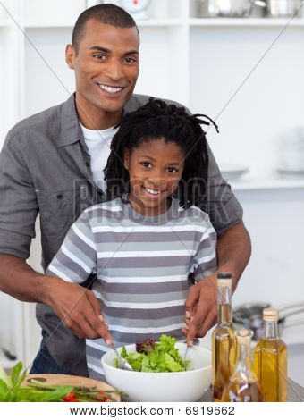 Smiling Little Boy Preparing Salad With His Father