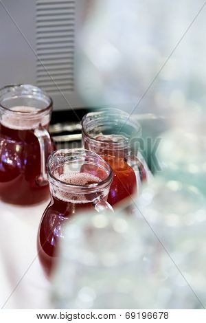 Topsy-turvy Glasses On Counter With Gugs Of Red Drink