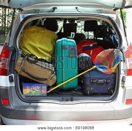 Trunk Of The Car With Fishing Net And Luggage Bags Ready For The Summer Holidays