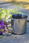 picture of ferrous metal  - metal cup for a hike on the table beside purple flowers - JPG