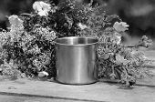stock photo of ferrous metal  - metal mug campaign is on the gray wooden table with a bunch of different wildflowers - JPG