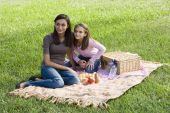 Girls sitting on picnic blanket on grass in park