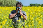 picture of hay fever  - man in field blowing his nose and suffering from hay fever - JPG
