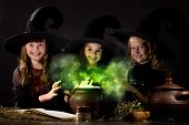 pic of witch  - Three little Halloween witches reading spell above pot - JPG