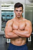 stock photo of shirtless  - Serious shirtless young muscular man standing in gym - JPG