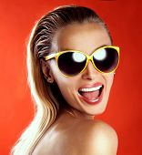 picture of posh  - Portrait of happy smiling blonde woman wearing fashionable sunglasses looking at camera - JPG