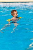 stock photo of floaties  - Happy boy swimming with floaties in swimming pool - JPG