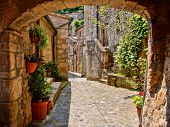 picture of cobblestone  - Arched cobblestone street in a Tuscan village - JPG