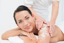 picture of scrubs  - Peaceful brunette getting a salt scrub beauty treatment in the health spa - JPG