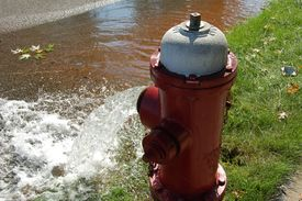 pic of gushing  - A fire hydrant gushing water into a city street - JPG