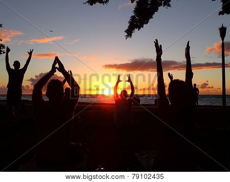 People Do Sunset Yoga For Charity On Waikiki Beach With Plane In Air And Boat In Water And Sun Setti