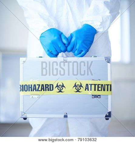 Close-up of medical case with biohazard symbol in scientist gloved hands