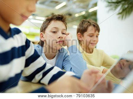 Tired schoolboy looking at digital tablet display with indifferent expression