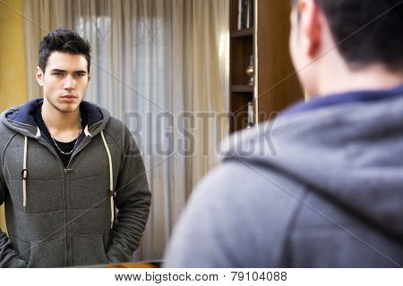 Handsome young man looking at himself in mirror at home
