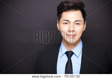 Smiling Businessman Standing Before Black Background