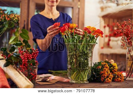 Flower seller putting flowers into a vase